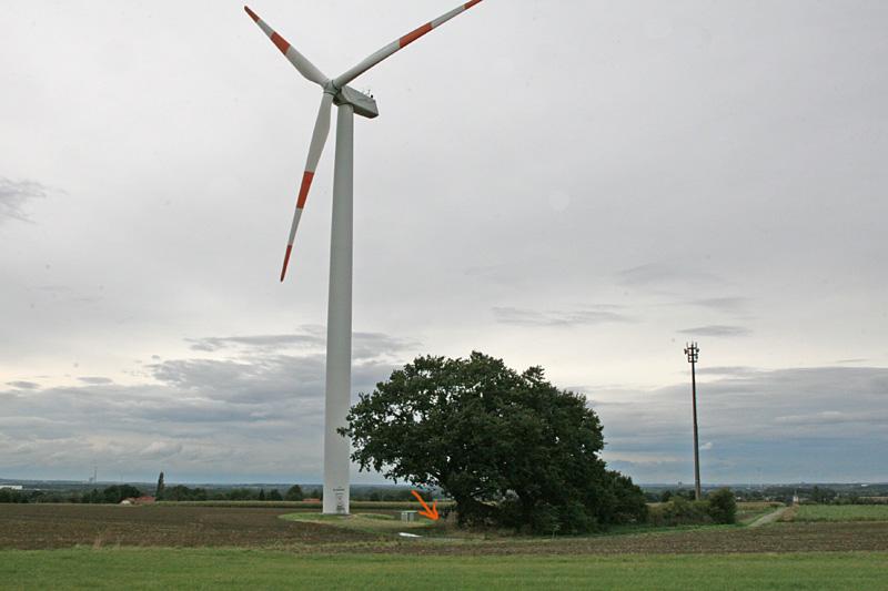 Der relativ kurze Mast mit den weit nach unten reichenden Rotorblättern - direkt hinter den Eichen..., 25.09.2012 Foto: Bernhard Glüer